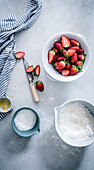 A still life with strawberries, flour, sugar and lemon zest