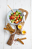 Breakfast eggs with avocado and tomato salad and bread sticks