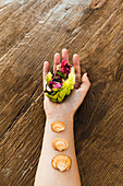 Hand of woman holding vegetarian rainbow lettuce wrap with seashells on wrist
