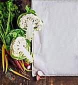 Fresh vegetables next to a white kitchen towel