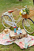Bicycle and vintage picnic suitcase on blanket