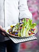 Mann serviert persischen Salat (Romanasalat mit Gemüse und Essblüten)