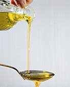 Pouring a spoonful of oil