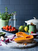 Stilleben mit Butternusskürbis, roten Zwiebeln, Tomaten und Zitronen