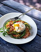 A poached egg with bacon and green peppers