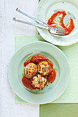 Artichokes with bread and cheese filling on herb tomato sauce