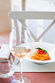 Restaurant table with a plate of spaghetti with tomato sauce