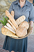 Girl holding a basket of various freshly baked homemade breads