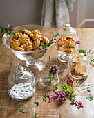 Biscuits and sugared almonds in glass jars bowls