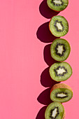 A row of kiwi halves on a pink background