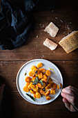 Pumpkin gnocchi with sage on a rustic wooden table
