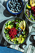 Salad bowls with avocado, beetroot, cucumber and blueberries