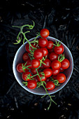 Fresh cherry tomatoes in a small bowl in front of a dark background
