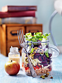 Vegeterian lunch salad in a jar with apples, beans, red pepper, pistachios and bulgur