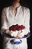 Woman serving Red Berry Pavlova