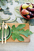 Fig leaf used as name card on wooden board next to place setting