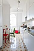 Küchenbereich mit weißer Küchenzeile abgetrennt durch deckenhohe Raumteilerregale