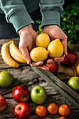 Hände halten drei Zitronen