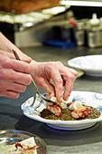 Preparing grilled octopus and squid, braised lentils and salsa verde