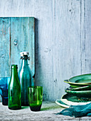 Still life with green and blue plates, glasses and bottles
