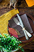 A rustic spring place setting decorated with leaves and green plants