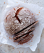 A round spelt whole grain bread on paper, sliced