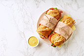 Fresh big baguette sandwiches with bacon, chedder cheese, mustard, lettuce and vegetables