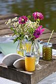 Picknick am See mit Getränken, Dekofischen und Blumen in Glasflaschen