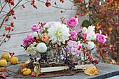 Floristische Dekoration mit Rosen, Dahlien, Hagebutten und Beeren vom wilden Wein