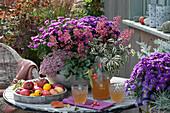 Herbstlich bepflanzte Schale mit Aster, Purpurglöckchen, Polster-Fetthenne 'Painted Pebble' und Salbei 'Tricolor', Dekanter und Gläser mit Apfelsaft, Äpfel und Zierquitten