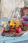 Dekanter und Gläser mit Apfelsaft, Holzscheibe als Untersetzer, Apfel und Hagebutten als Dekoration