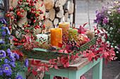 Herbstliche Dekoration mit Kerzen, Äpfeln, Maronen, Hagebutten und wildem Wein, Hagebutten-Kranz am Brennholz