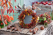 Kranz aus Hagebutten und Herbstlaub an Eimer mit Utensilien gelehnt, Hagebutten-Strauß, Tulpenzwiebeln und Pflanzschaufel
