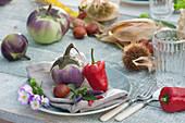 Aubergine, Paprika, Marone, Chili und Blüten vom Hornveilchen als Tellerdeko