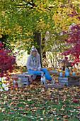 Umgedrehte Weinkisten als Sitzgruppe unterm Ahornbaum, Frau mit Teetasse, Hund Zula