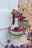 Tasse als Windlicht am Türgriff, dekoriert mit Zieräpfeln, Hagebutten und Beeren vom Liebesperlenstrauch
