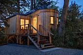 Tiny House aus Holz auf Stelzen mit Treppenaufgang und kleiner Veranda bei Abendbeleuchtung