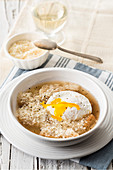 Meat broth with bread, parmesan and a poached egg