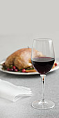 A glass of red wine in front of a festive roast duck