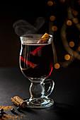 Dampfender Glühwein mit Zimtstange im Glas