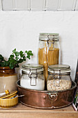 Pasta and oatmeal in storage jars in cake tin