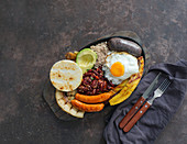 Bandeja paisa - Columbian fried pork belly, black pudding, sausage, arepa, beans, fried plantain, avocado egg, and rice