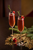 Pair of glasses of red cocktail decorated with berries and green herbs