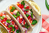 Homemade Mexican Tacos with fresh vegetables and chicken on white background