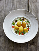 New potatoes with a white wine sauce, mixed herbs and colourful caviar