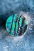 Blauer Mirror Glaze Cake mit Zuckerperlen und Zuckersternen