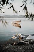 Sektflasche mit Gläsern, Sonnenhut, Sandaletten und Decke am Steinufer eines Sees
