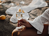 Woman wearing beach dress holding glass of sparkling wine