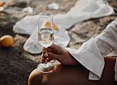 Frau im Strandkleid mit Sektglas in der Hand