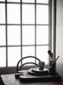 Kitchen utensils and crockery on chopping board on wooden table in front of window